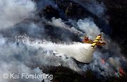 Valencia, 16/02/2005. Un hidroavión suelta su carga sobre los montes cercanos a Llauri, donde desde anoche lleva activo un incendio forestal.