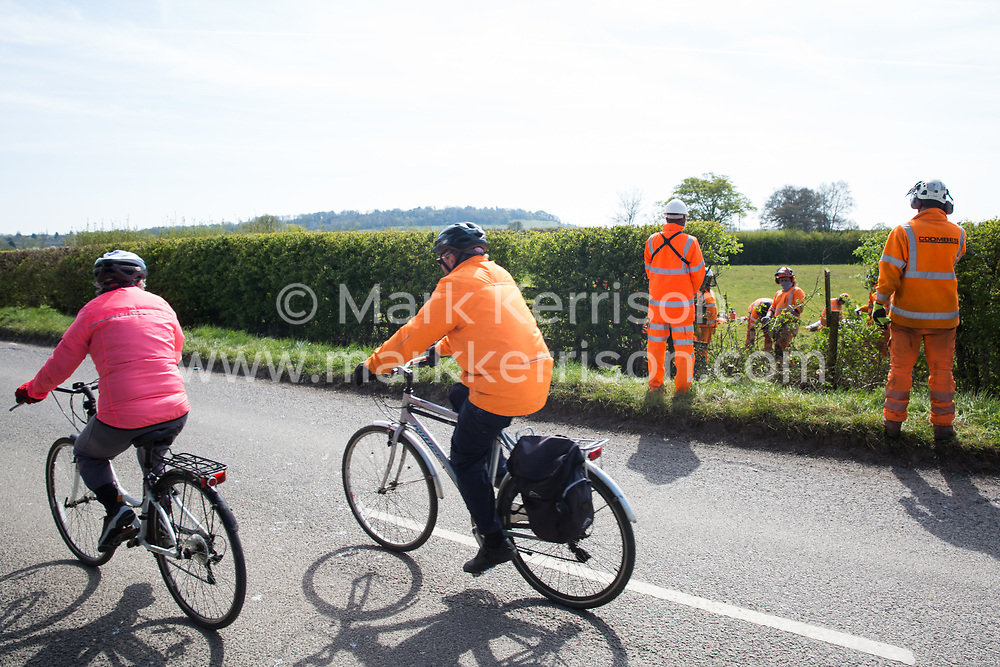 Two local cyclists pass tree surgeons contracted to HS2 clearing a section of hedgerow for a temporary access road for the HS2 high-speed rail link on 26th April 2021 in Quainton, United Kingdom. Environmental activists continue to oppose the controversial HS2 high-speed rail link from a series of protection camps along its Phase 1 route between London and Birmingham.