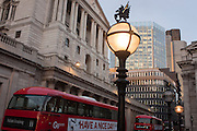 A buses and traffic pass below, early evening lighting illuminates the street, below the Bank of England, on 9th December 2016, in the City of London.