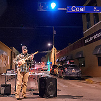 011114       Cable Hoover<br /> <br /> Musician and luthier Scott Halliday plays one of his handmade cigar box guitars in the intersection of Coal Avenue and Second Street during ArtsCrawl in downtown Gallup Saturday.