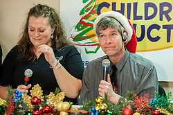 Radio personalities Molly King and Pat Kelly choke back tears after announcing a recordbreaking $415,500 collection in the 31st Annual Children's Christmas Auction on Saturday, December 8, 2012.  (Alan MacRae/for the Laconia Daily Sun)