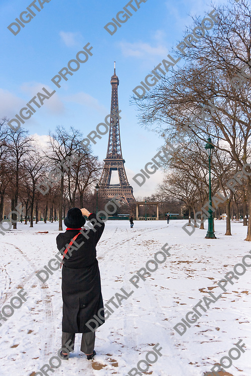 A tourist takes a photo of the eiffel tower in the snowy Champs de Mars during winter