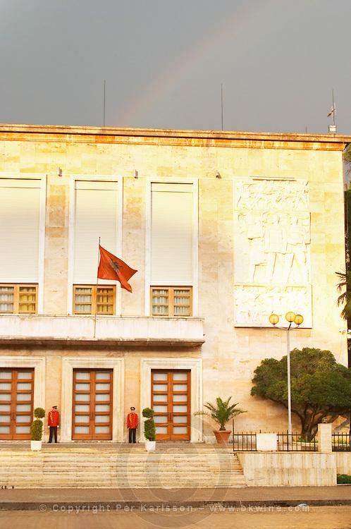 The presidential president's palace with Albanian flag and honour guard. On the boulevard Bulevardi Deshmoret e Kombit. Rainbow in the sky. Tirana capital. Albania, Balkan, Europe.