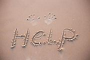 HELP written in the damp sand on a beach