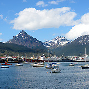 A view of Ushuaia Port from across the harbor, with the distinctive, sharp triangle-shaped Monte Olivia (Mount Olivia) in the background.