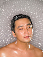 Headshot of a shirtless asian male (40-50 years old).