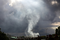 © Licensed to London News Pictures. 17/08/2020. London, UK. Smoke billowing from chimneys under thunderclouds, over north London. Photo credit: Dinendra Haria/LNP