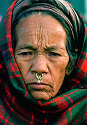 A woman from the Kathmandu valley in Nepal wearing nose jewels in the traditional way.  Her head is covered with a tartan shawl.