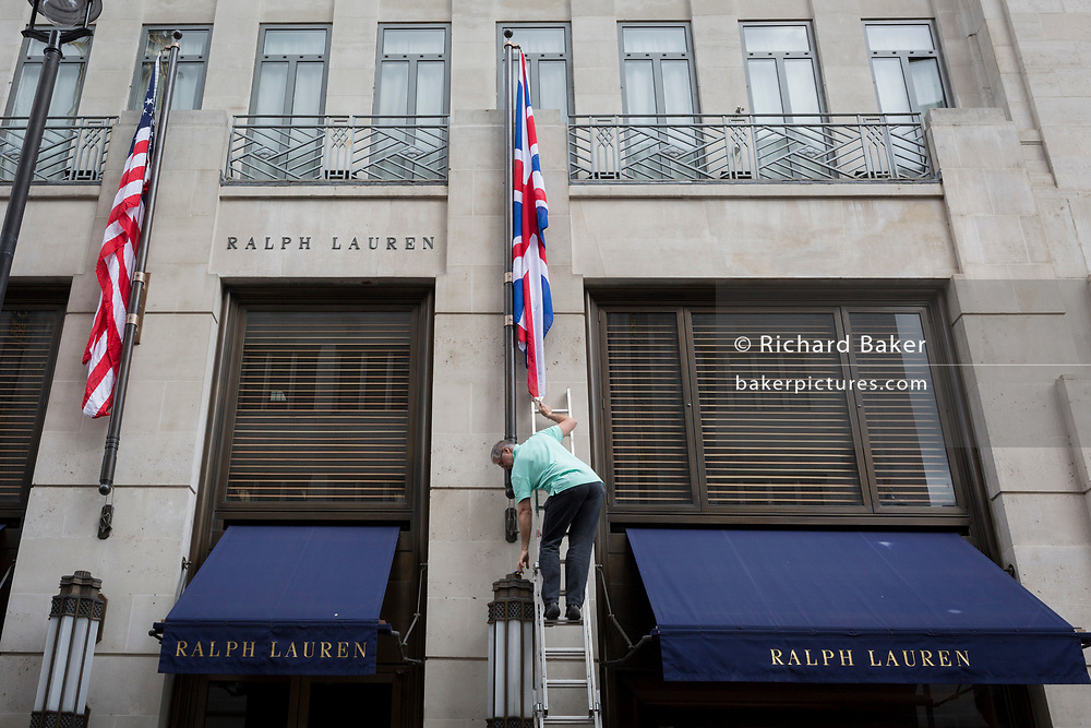 An employee renews the US and British flags outside the American clothing retailer's Bond Street address, on 5th June 2019, in London, England. outside American clothing retailer Ralph Lauren's Bond Street address, on 5th June 2019, in London, England.