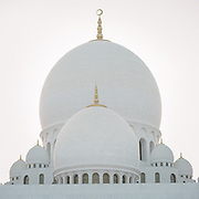 Made of bright white marble, the famous Sheikh Zayed Grand Mosque at sunset.
