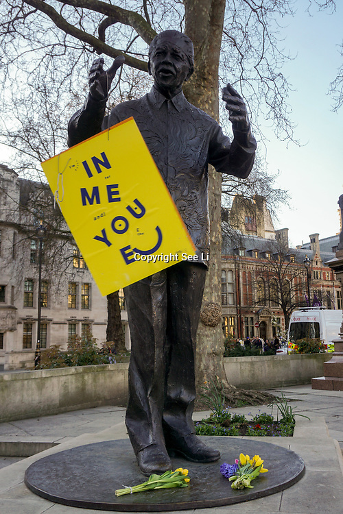 A placard hanging at the Statue of Nelson Mandela, Parliament Square after Unite for Europe March in Parliament square, on 25th March 2017. Placards and flowers hanging at the Parliament aftermate,London,UK. by See Li