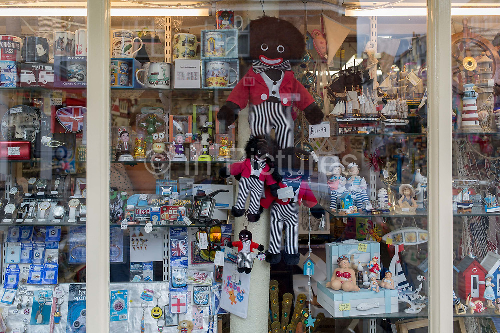 Detail of a shop window selling seaside holiday trinkets including different sizes of Golliwogs, on 14th July 2017, at Scarborough, North Yorkshire, England. The golliwog is a black fictional character from the late 19th century depicting a rag doll. It was reproduced by commercial and hobby toy-makers as a childrens toy and had great popularity in the UK and Australia into the 1970s. The doll has black skin, eyes rimmed in white, clown lips and frizzy hair and was seen, along with the teddy bear, as a suitable soft toy for a young boy. The image of the doll has become the subject of controversy as the Golliwog has been seen as a depiction of black people, accused along with pickaninnies, minstrels, mammy figures, and other caricatures as being racist. The golliwog has been described as the least known of the major anti-Black caricatures in the United States.