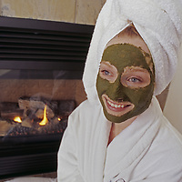 A woman wears a robe and facial treatment.