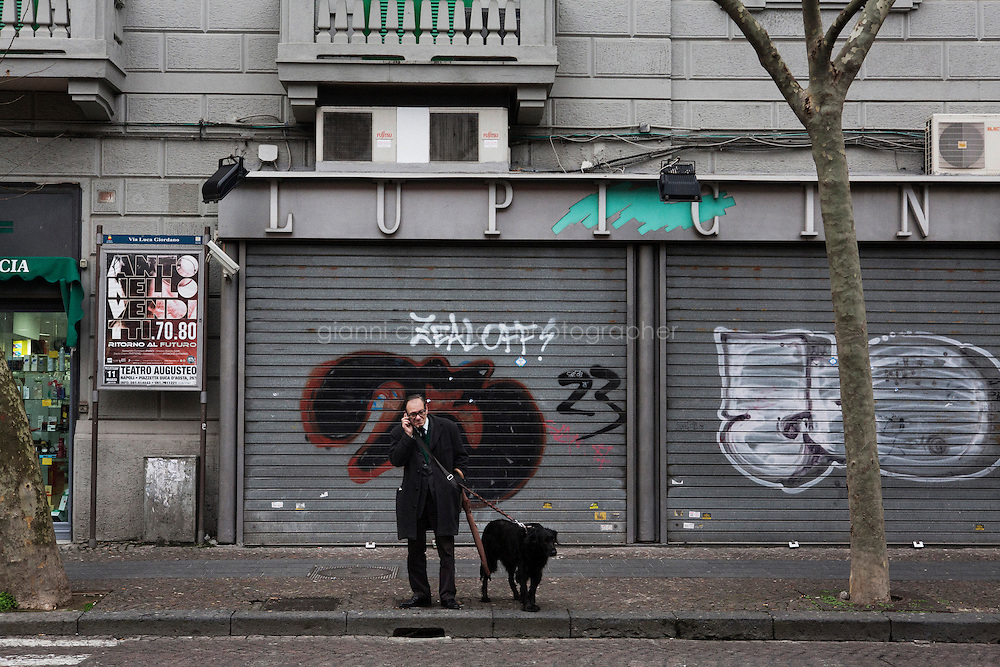 NAPLES, ITALY - 23 January 2014: A man walks his dog in the Vomero-Arenella neighborhood, where a pilot project to keep streets clean from dog excrements was started, in Naples, Italy, on January 23rd 2014.<br /> <br /> The city of Naples started a pilot project in the district of Vomero-Arenella aimed at busting irresponsible dog owners from leaving their pets' feces in the street. Blood samples are being collected from the approximately 8,000 dogs living in the neighborhood of 110,00 inhabitants. (the city of Naples counts a total of 960,000 people and 60,000 dogs). In a few months city street cleaners  will locate the excrements, call the police who will send a sample to a laboratory where DNA will be extracted and compared with the results of blood samples.