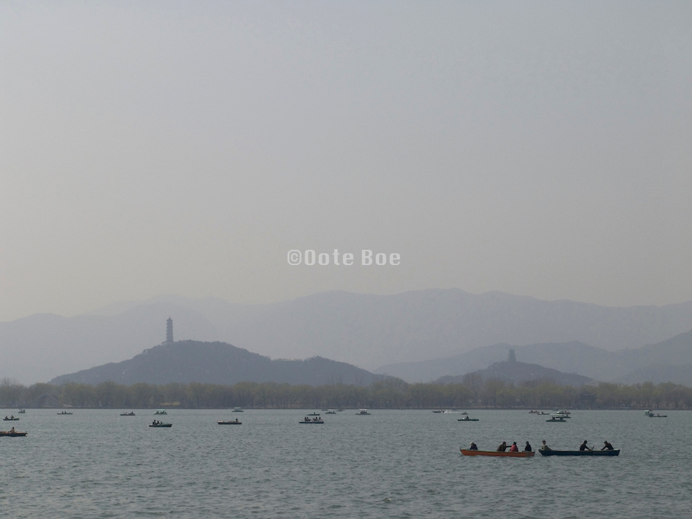 lake at the Summer Palace with rowboats and mountains in the distance Beijing