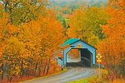 Autumn colors surround the covered bridge - Pont Des Draveurs - across the Petite rivière Neigette.<br />Sainte-Blandine<br />Quebec<br />Canada