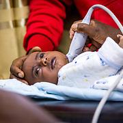 INDIVIDUAL(S) PHOTOGRAPHED: Getaneh Mintasenot. LOCATION: Felege Hiwot Referral Hospital, Bahir Dar, Ethiopia. CAPTION: Getaneh Mintasenot calmly receives an ultrasound test, performed by Dr. Getnet Yenew.