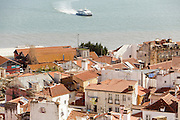 A catamaran crossing Tagus River seen from Portas do Sol lookout in Lisbon.