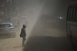 March 22, 2019 - Kathmandu, Nepal - A man crosses the dusty road on the way to Gokarna Forest Resort in Kathmandu, Nepal on Friday, March 22, 2019. (Credit Image: © Skanda Gautam/ZUMA Wire)
