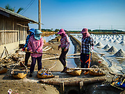 20 FEBRUARY 2019 - BAN LAEM, PHETCHABURI, THAILAND: Salt workers walk to a salt field on one of the first days of the 2019 salt harvest in Ban Laem, Thailand. Ban Laem's salt fields are expanding because salt harvesters in Samut Sakhon and Samut Songkhram,  which are closer to Bangkok, are moving to Ban Laem as their land is turned into industrial parks.      PHOTO BY JACK KURTZ