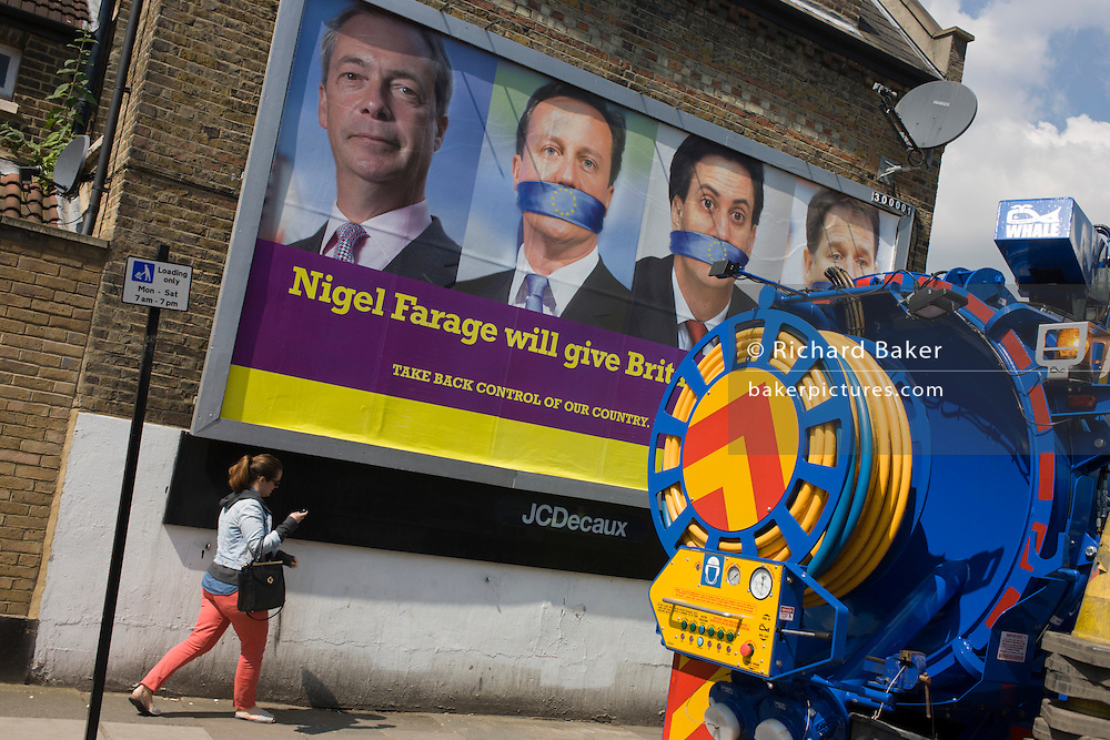 A voter walks past a council drains cleaner near an anti-EU membership 'UK Independence Party's (UKIP) political billboard shows leader Nigel Farage and a gagged Prime Minister David Cameron, Labour party leader Ed Milliband and (coaltion) Deputy PM Nick Clegg - all silent against a bullying European Union, seen in East Dulwich - a relatively affluent district of south London. The ad is displayed before European elections on 22nd May.