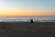 A lifeguard chair, turned on its side for the night, is on the beach as dawn arrives.