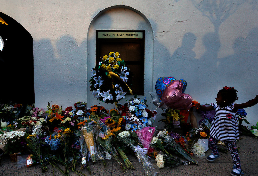 Mourners pass by a make-shift memorial, <br /> Thursday, June 18, 2015 on the sidewalk of in front of the Emanuel AME Church following a shooting Wednesday night in Charleston, S.C. Shooting suspect Dylann Storm Roof, 21, was captured without resistance in North Carolina Thursday after an all-night manhunt, Charleston's police chief Greg Mullen said. (AP Photo/Stephen B. Morton)