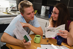 Couple sitting at the kitchen table reading bank information translated into Polish,