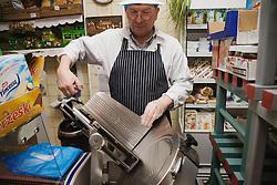 Polish Shop owner cleaning meat slicer,