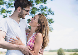 Mid adult couple smiling at each other in front of tree in the countryside, Bavaria, Germany