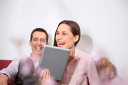 Young couple holding tablet computerlaughing