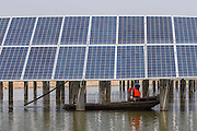 LIANYUNGANG, CHINA - MARCH 16: (CHINA OUT)<br /> <br />  Electricians boat to inspect the solar panels in a fish pond on March 16, 2016 in Lianyungang, Jiangsu Province of China. A 150,000-square-meter photovoltaic station including over 40,000 solar panels built in a fish pond began to make electricity in Lianyungang.<br /> ©Exclusivepix Media