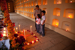 North America, Mexico, Oaxaca Province, Oaxaca, Pantheon San Miguel Cemetery, family at altar in hall with rows of tombs, some dating back to the 1800s, lit with candles for annual Day of the Dead (Dias de los Muertos) celebration in November