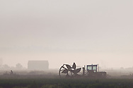 Florida, New York - Farm machinery is parked in a field as early morning fog burns off in the background on July 22, 2014.
