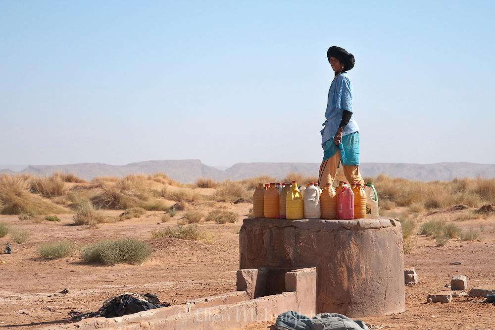 Nomadic Berber woman filling water bottles in the Sahara Desert, Morocco