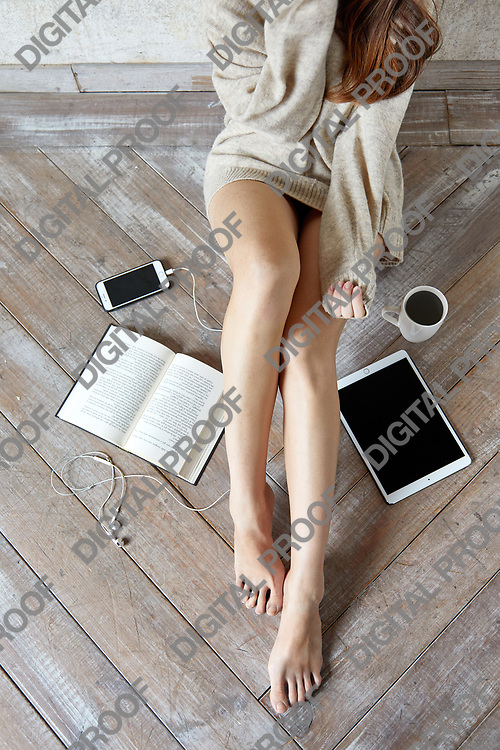 Concept of a Lazy day with a  young woman wearing a sweater sitting on wooden floor with a mobile phone, headphones, an electronic tablet and a paperback book, copy space, top view, vertical