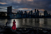 Woman in red agaisnt the Brooklyn Bridge at sunset