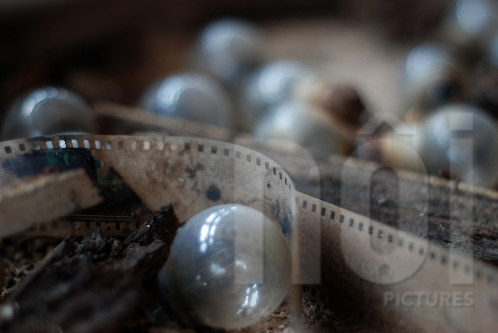Strip of old film lays on the ground in the middle of bulbs. Abandoned cinema of Bouasavanh, Vientiane, Laos, Asia