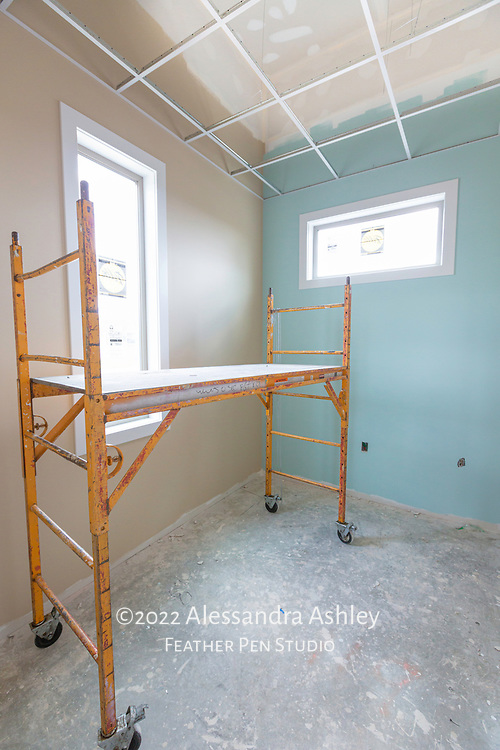 Interior wall painting begins at building site of new physical therapy and wellness center. Meditation room shown, with main and accent colors painted and ceiling grid installed.