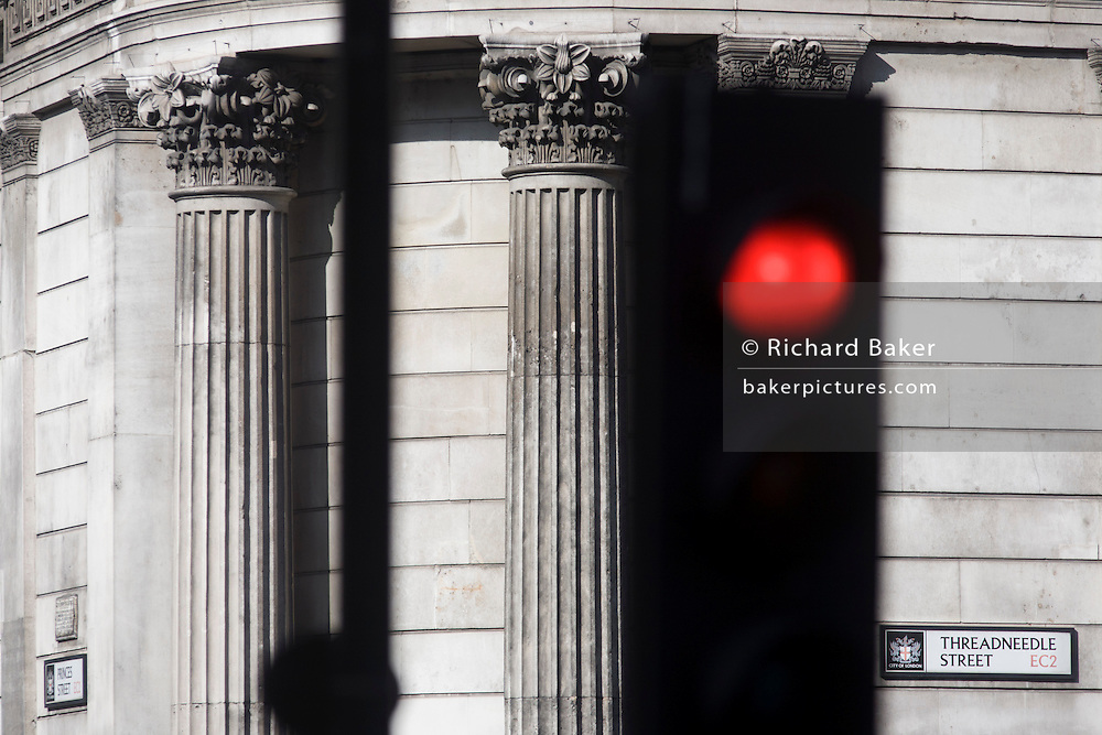 Red Stop traffic light and pillars with City of London sign for Threadneedle Street EC2 at Bank Underground station in the heart of the capital's financial district.