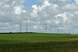 High Voltage wires string together a double row of distribution towers beneath a cloudy sky and over a field of soybeans disappearing over the horizon