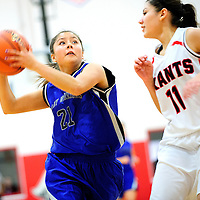 121512  Adron Gardner<br /> <br /> Navajo Pine Warrior Kaitlin Chee (21) drives down the lane past Grants Pirate Veronica Lopez (11) in the Eddie Pena Holiday Classic championship at Grants High School Saturday.