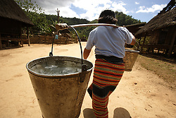 An unnamed woman carries heavy buckets of water back from a standpipe,  Ban Chaling, Dakcheung, near Sekong, Lao PDR