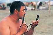 Horse trainer shaving<br /> Naadam horse race<br /> Jockey's aged 4-12 years and most often girls<br /> Ulaanbaatar race track<br /> Mongolia
