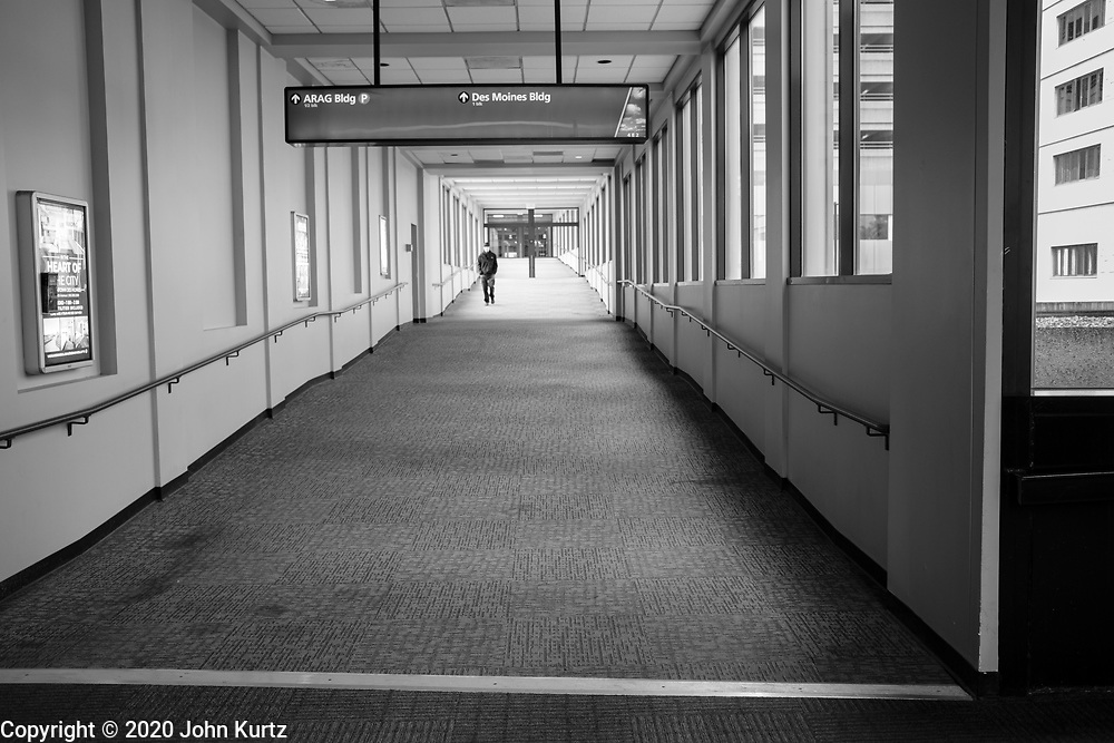 01 OCTOBER 2020 - DES MOINES, IOWA:  A person walks through an empty skywalk in downtown Des Moines. The skywalk system used to be crowded, especially on cold days, but since the pandemic struck and businesses moved employees to work from home the skywalks are deserted. The economy in downtown Des Moines is still feeling the affects of the COVID-19 shutdown ordered in March. Seven months after the shutdown, employers still have their workers working from home. Restaurants, barbershops, and retail are feeling the impact. Many have closed or cut back on workers and hours.       PHOTO BY JACK KURTZ