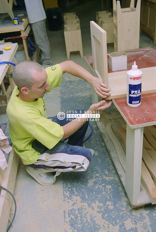 Cabinet maker assembling blanket box using nails and glue,