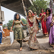 A bride, accompanied by her friends and relatives, leaves the beauty salon in west Delhi on her way to the wedding venue. <br /> Delhi, 2010