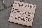 Homeless begging sign left on the pavement on 5th March 2021 in London, England, United Kingdom. The sign reads I am very hungry, God bless.