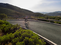 Woman riding bike against mountain during sunset