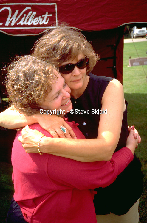 Friends age 48 embracing at fathers funeral.  St James  Minnesota USA
